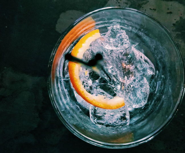 High angle view of ice in glass, gin and tonic