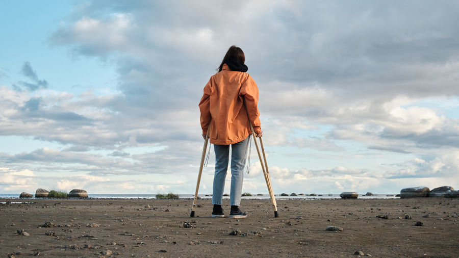 A woman on crutches walks along the shore of the lake.