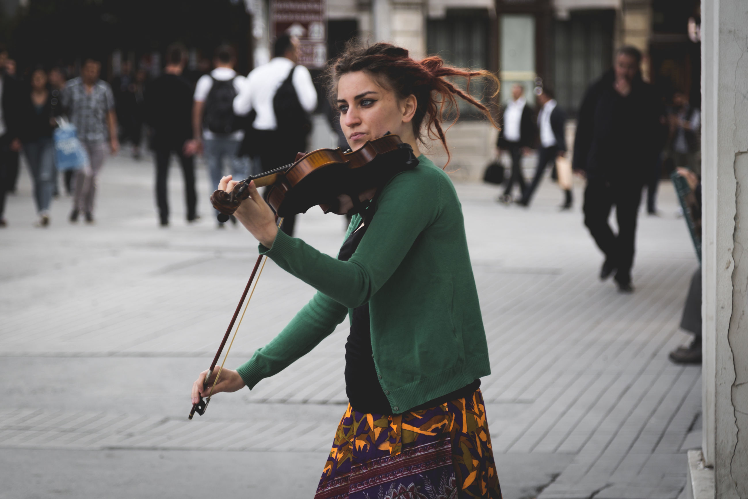 focus on foreground, incidental people, one person, holding, real people, lifestyles, young adult, outdoors, playing, music, day, young women, musician, beautiful woman, city, adult, people