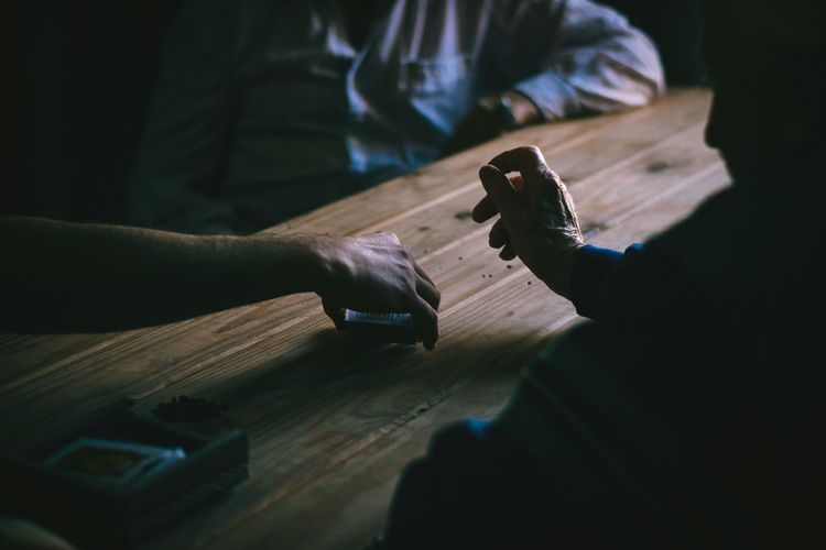 Male friends playing cards on wooden table