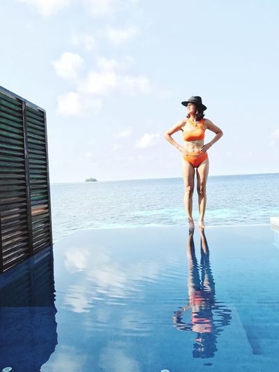 Woman in bikini standing on infinity pool against sky