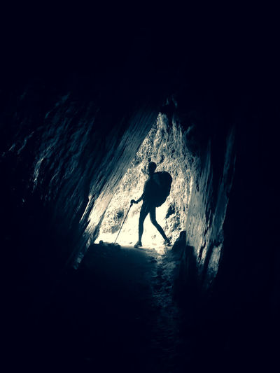 Silhouette man on rock in cave