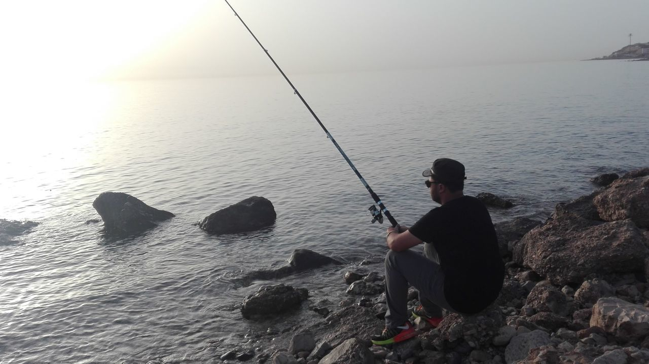 sea, fishing, fishing pole, horizon over water, fishing rod, water, real people, one person, nature, tranquil scene, beauty in nature, weekend activities, outdoors, holding, tranquility, leisure activity, standing, sitting, fishing tackle, scenics, men, full length, day, clear sky, sky