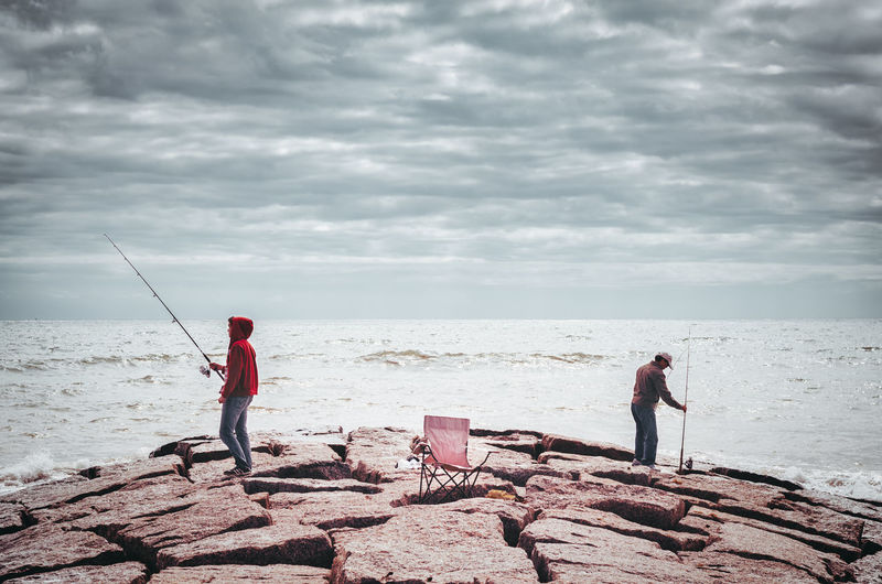 Men fishing by sea against cloudy sky during sunny day