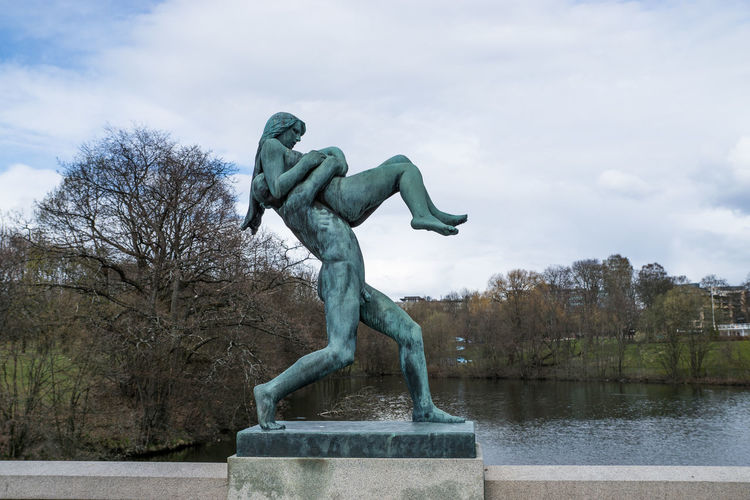 Low angle view of statue by lake against cloudy sky at gustav vigeland sculpture park