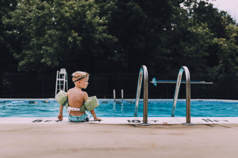 Rear view of shirtless boy wearing water wings sitting at poolside