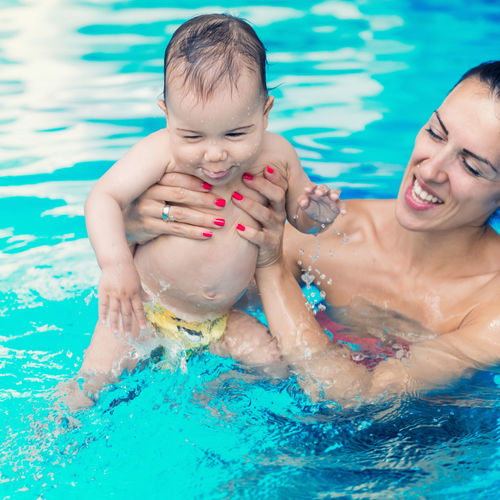 Close-Up Of Mother Holding Cheerful Shirtless Toddler Son In Pool