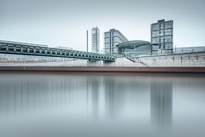 bridge over spree river in berlin against sky Berlin Bridge - Man Made Structure Building Building Exterior Central Station City Cityscape Copy Space Fine Art Hauptbahnhof Berlin Long Exposure Modern Architecture Muted Colors Philipp Dase Reflections In The Water Spree River Winter Discover Berlin