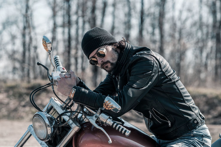Mid adult man sitting on motorcycle in forest