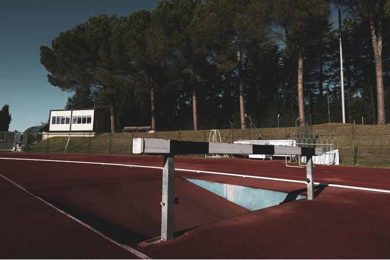 running track hurdle Tartan Track Athletics Sport Running Stadium Competition Speed Lanes Hurdle Hedge Obstacles Wooden Playing Field Outdoors Grass Empty Absence Nature Plant Tree
