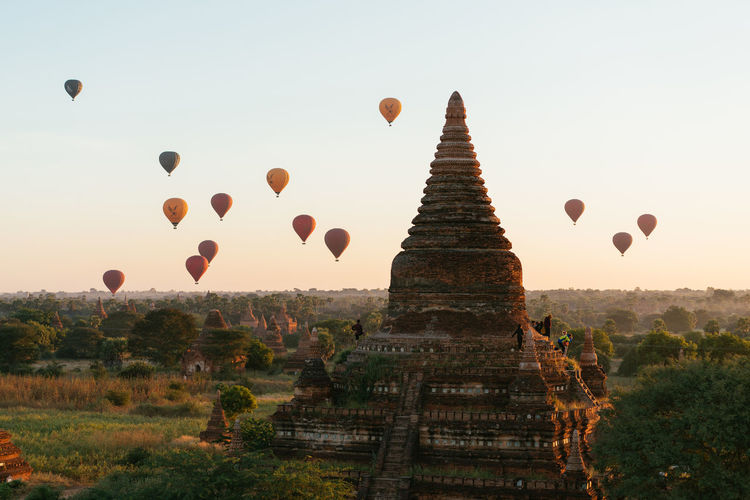 View of hot air balloons over temple against sky