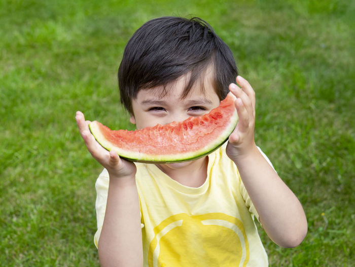 Portrait of boy holding watermelon while standing outdoors
