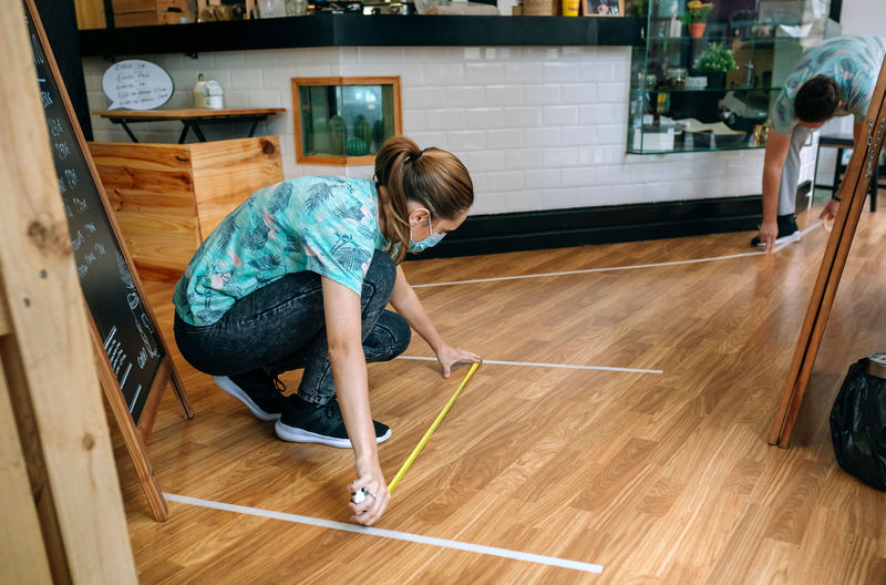 Side view of woman playing on hardwood floor at home