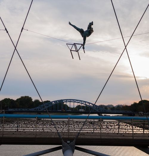 Almost Symmetrical Gymnastics Sculptures Cracow Bridge - Man Made Structure Sky Suspension Bridge Bridge River Podgórze Bernatka Kladka KładkaBernatka In The Middle Geometry Geometric Architecture Man On Chair With Chair Flying Chair Metal Sculpture Krakow Poland Battle Of The Cities Sunset Chair In The Air