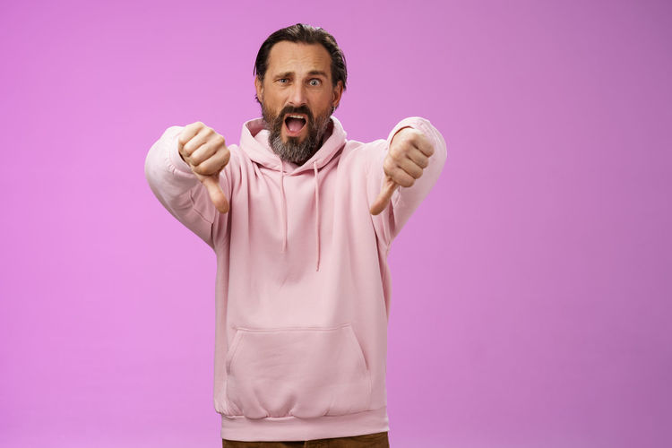 Displeased man showing thumbs down against purple background