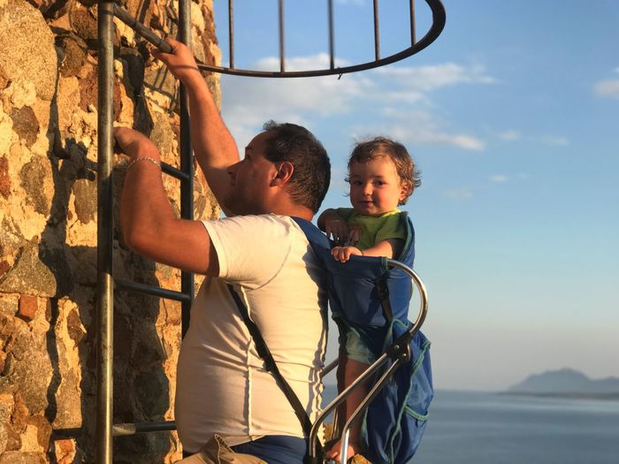 Side view of father climbing ladder while carrying son against sky