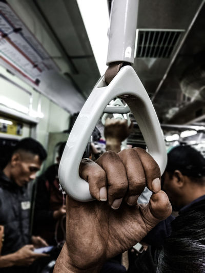 Cropped Hand Of Man Holding Handle In Train