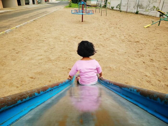 High Angle View Of Girl Sliding On Slide At Park