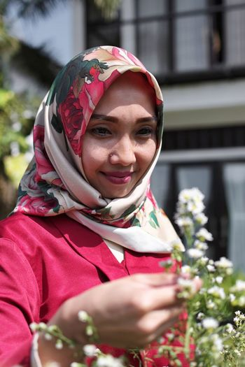 Smiling Mid Adult Woman Wearing Hijab Looking Flowers In Park