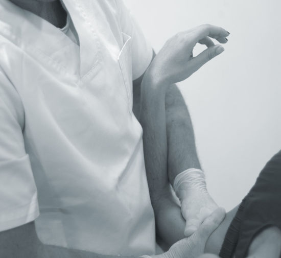 Midsection of physical therapist massaging patient