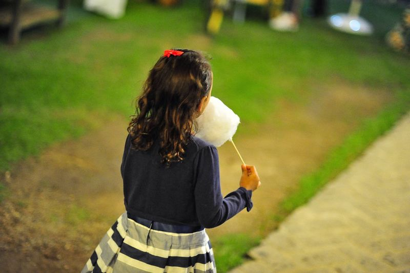 Rear view of girl eating cotton candy while walking at park