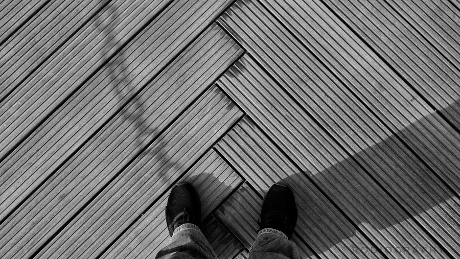 Low section of person standing on wooden floor