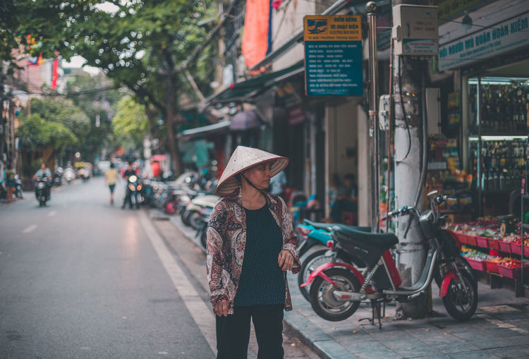 Quaint. Adult Asian Style Conical Hat Bicycle Building Exterior City Hat Land Vehicle Mode Of Transport One Person People Real People Street Women An Eye For Travel Adventures In The City International Women's Day 2019