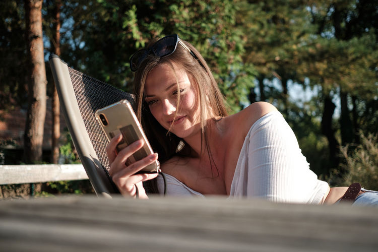 Woman using mobile phone while sitting on book