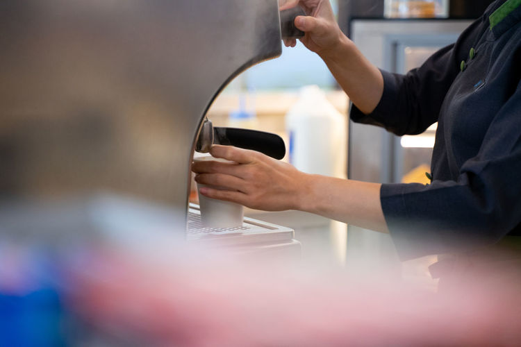 Midsection of man working with coffee