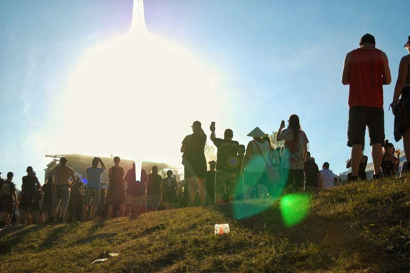 People standing on field against sky