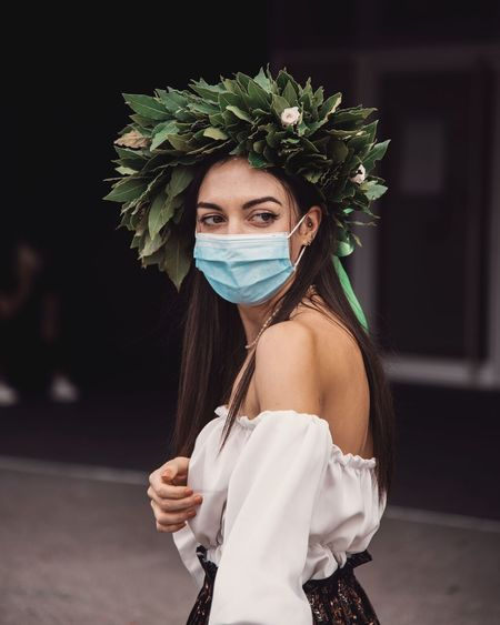 Close-up of young woman wearing mask standing outdoors