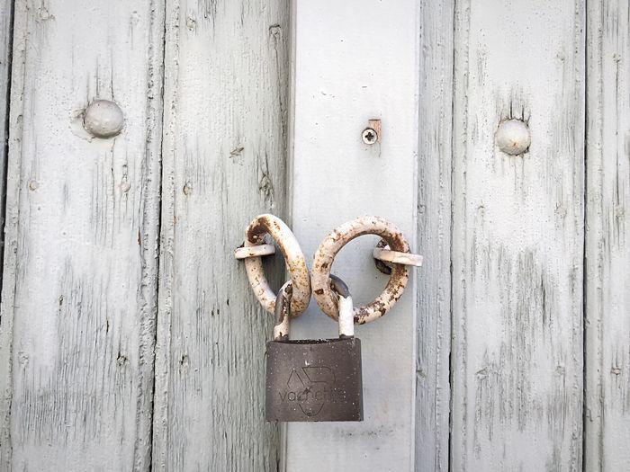 Rusty padlock on closed wooden door