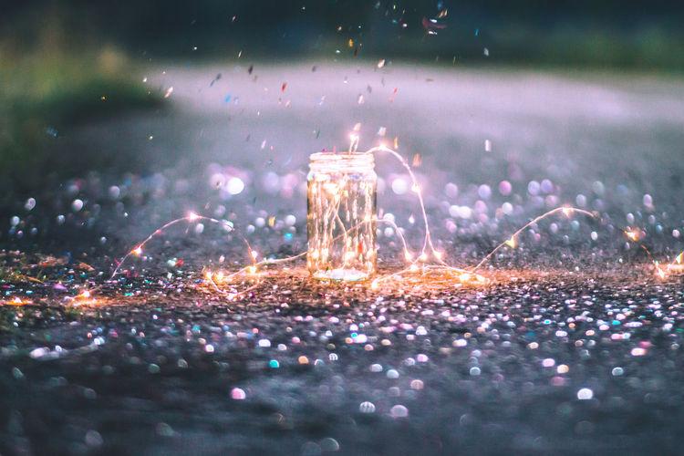 Confetti falling on illuminated string light in jar on road