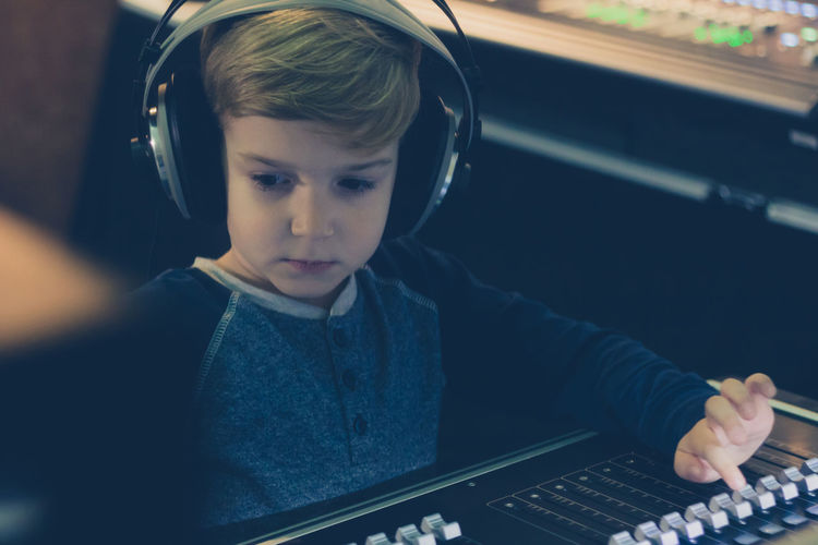 Cute boy mixing music in recording studio