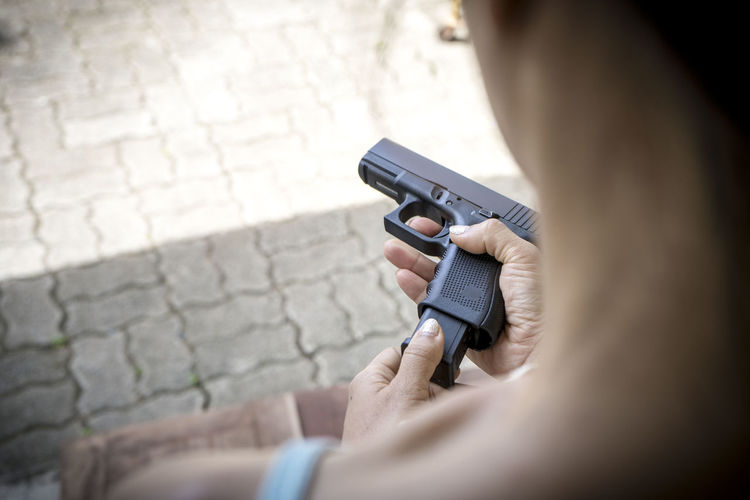 Woman Holding Handgun On Footpath
