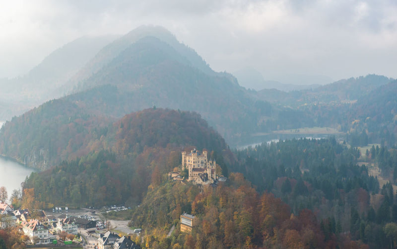 Hohenschwangau Castle with Autumn colors, Fussen, Germany Mountain Architecture Scenics - Nature Tree Beauty In Nature Nature Mountain Range Built Structure Sky Fog Building Exterior Environment Tranquil Scene Day Plant No People Tranquility Building High Angle View Outdoors TOWNSCAPE