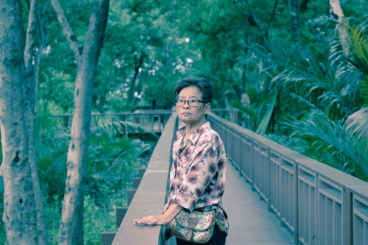 Mature woman standing on footbridge in forest