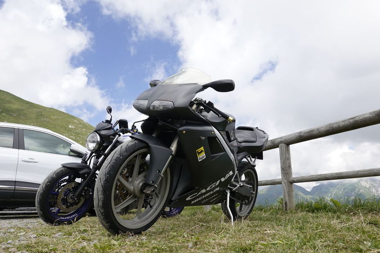 Motorcycle parked on land against sky