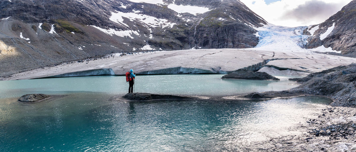 Full length of hiker standing on rock amidst glacial lake
