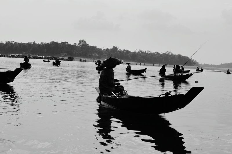 Silhouette men fishing on boat at lake