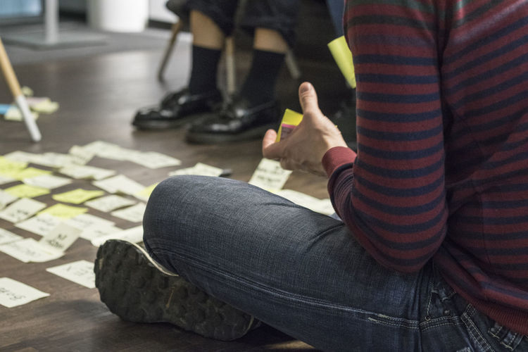 Low section of man holding adhesive note while sitting on floor