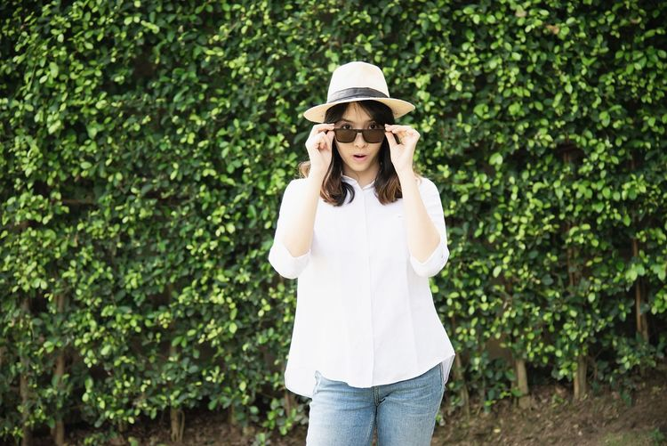 Portrait of young woman wearing hat and sunglasses while standing against plants