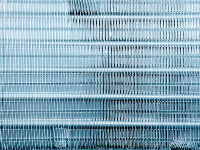 Close up aluminum fin of cooling condenser coil air condition system. abstract background.