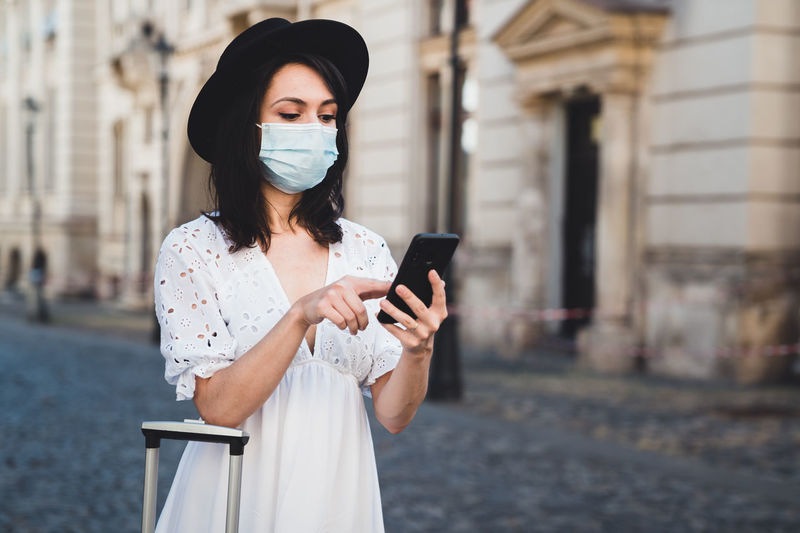 Woman wearing mask using smart phone standing on road