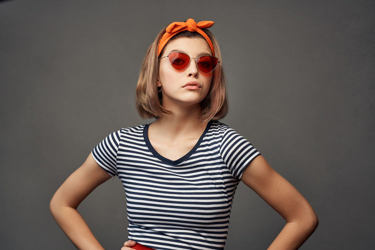 Portrait of beautiful young woman wearing sunglasses standing against gray background