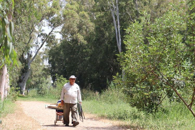 Full length of man sitting on seat against trees