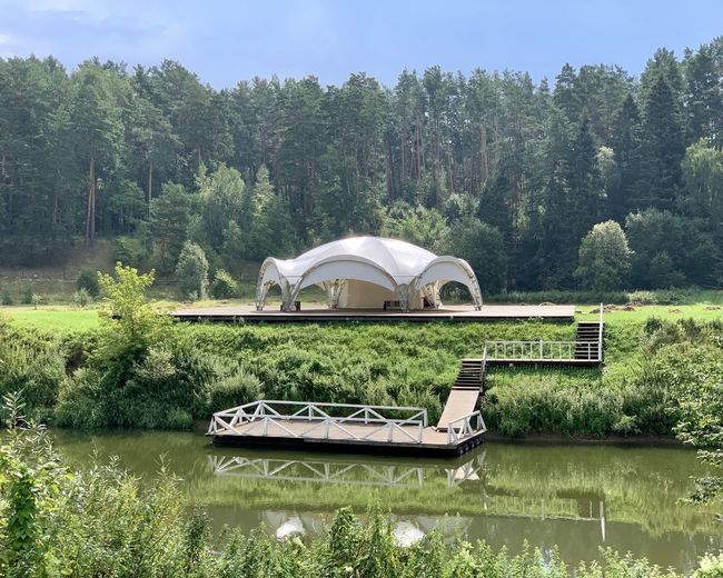 Built structure by lake against trees