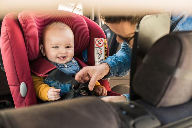 Portrait of cute baby sitting in car