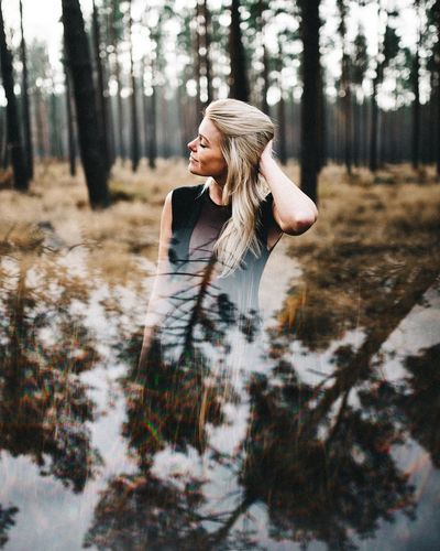 Double exposure young woman with hand in hair standing in forest