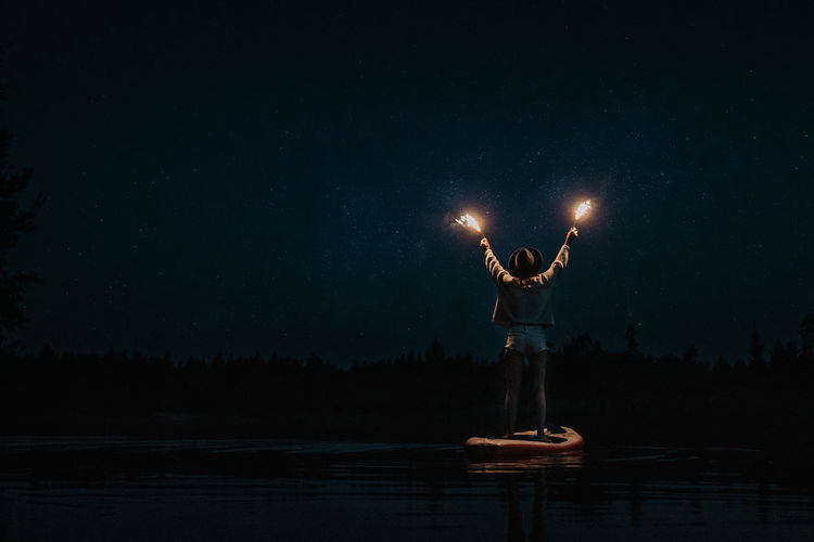 Shine Sparkler Woman Adult Arms Raised Astronomy Beauty In Nature Human Arm Human Limb Illuminated Lake Leisure Activity Limb Nature Nautical Vessel Night One Person Outdoors Scenics - Nature Sky Standing Stars Sup Water Women HUAWEI Photo Award: After Dark